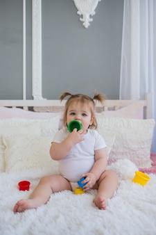 白いボディースーツを着た少女がカラフルなおもちゃでベッドで遊ぶ