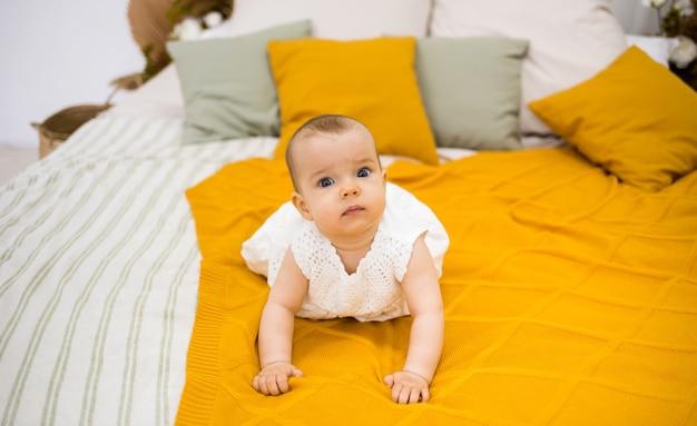 Маленькая девочка в белом хлопковом платье ползет по кровати