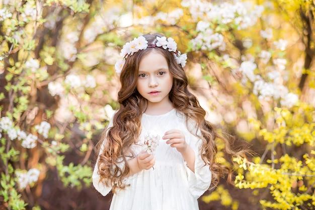 黄色い花を背景に白いドレスを着た少女。美しい少女との春の写真。花輪を持つ子供..