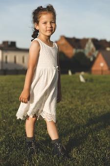 夏の芝生の上の白いドレスを着た少女