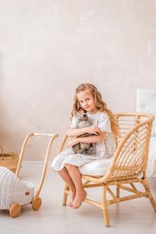 Маленькая девочка в белом платье сидит на стуле и обнимает пасхального кролика. ребенок в светлой комнате с игрушечным кроликом.