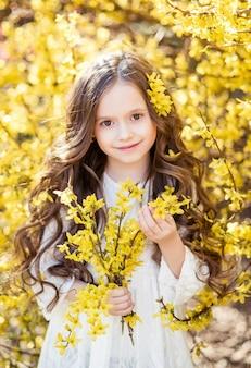 彼女の手に黄色い花を持つ白いドレスを着た少女。黄色い花を背景にした子供。子供の春の肖像画..