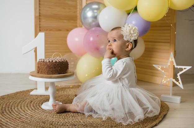흰색 휴가 드레스에 어린 소녀는 매트에 앉아 케이크를 먹고있다