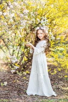 黄色い花を背景に白い長いドレスを着た少女。美しい少女との春の写真