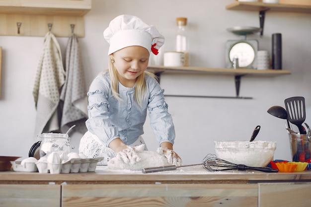 Маленькая девочка в белой шляпке готовит тесто для печенья