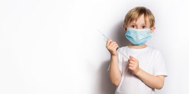 白いtシャツを着た少女と注射器を持った医師を演じる医療マスク