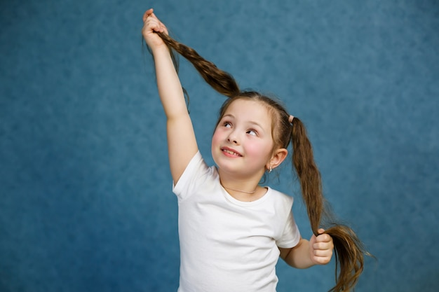 Маленькая девочка в белой футболке и джинсах дурачится с волосами