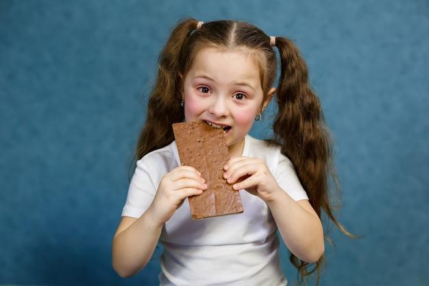 白いtシャツを着た少女がチョコレートのバーを食べる