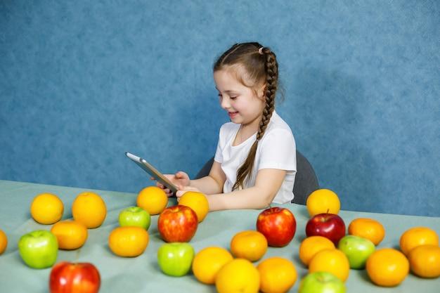 흰색 티셔츠를 입은 어린 소녀는 손에 태블릿을 들고 과일을 연구합니다