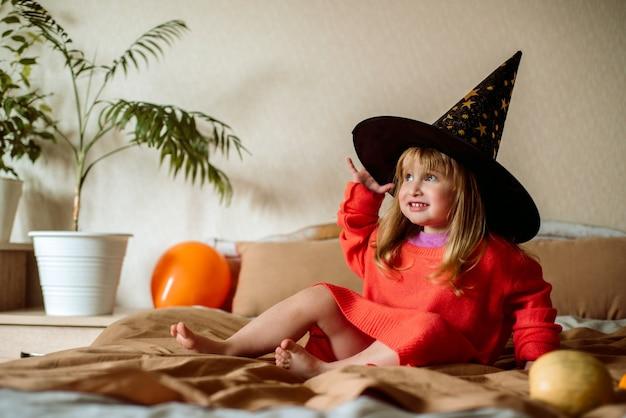 그녀의 손에 오렌지 공 마녀 모자에있는 어린 소녀. 할로윈 concept.active 게임 집에서. 감정적으로 웃고 침대에 뛰어 듭니다.