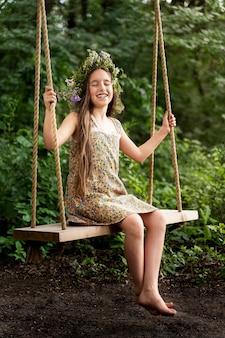 Маленькая девочка в венке из цветов катается на качелях и смеется