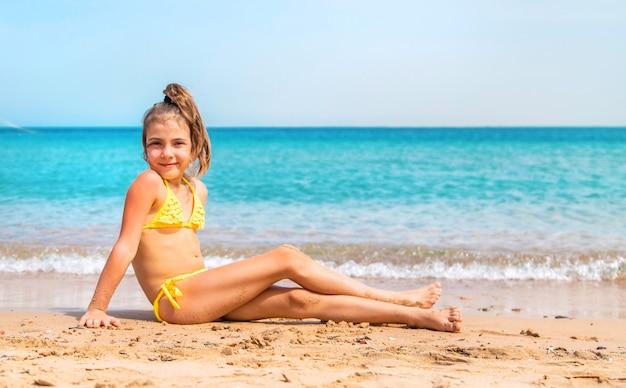 黄色いビキニの少女がビーチの砂の上に座っています