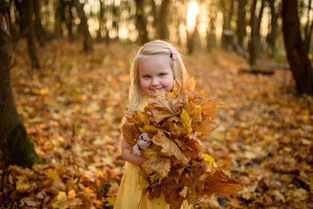 Маленькая девочка в желтом платье в парке осени. ребенок держит в руках пучок листьев. крупный план.