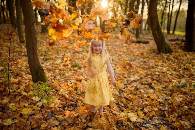 Маленькая девочка в желтом платье в парке осени. ребенок бросает листья.