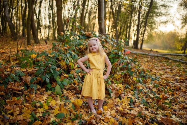 Маленькая девочка в желтом платье в парке осени.
