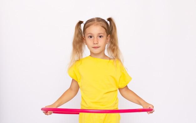 노란 드레스를 입은 어린 소녀가 아령을 들고 후프에 앉아 있습니다. 흰색 배경에 격리되어 있습니다.