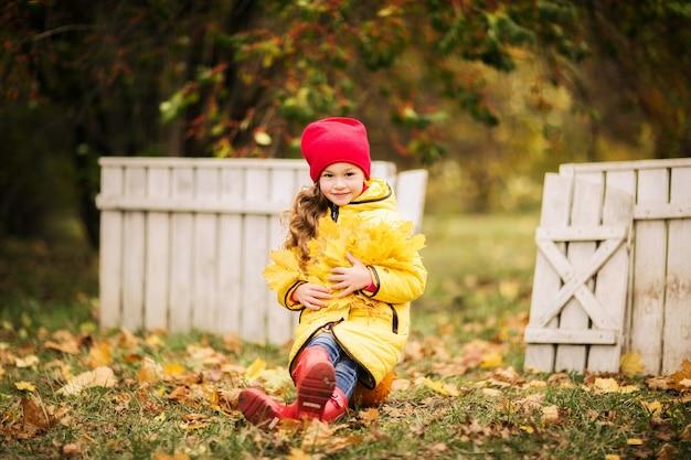 秋の公園の芝生の上に座っている黄色のレインコートの少女