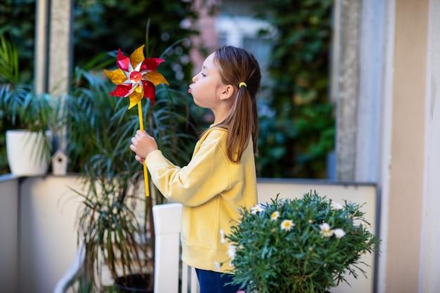 風車を吹いているバルコニーの黄色いスウェットシャツの少女。