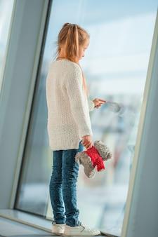 搭乗を待つ間大きな窓の近くの空港の小さな女の子