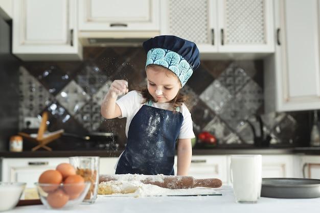 エプロンとシェフの帽子をかぶった少女がクッキー生地を広げています