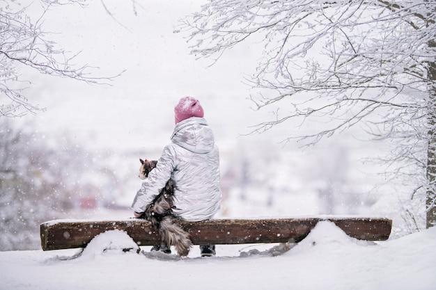 丘から広がる雪に覆われた風景を見ているベンチで視聴者に背を向けて座っている大きな猫と抱擁の少女。