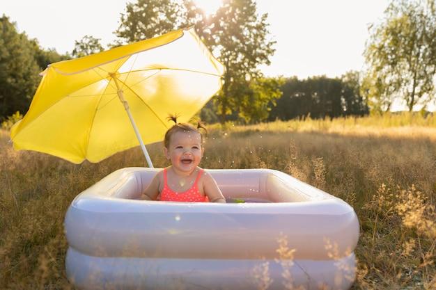 Маленькая девочка в надувном бассейне.