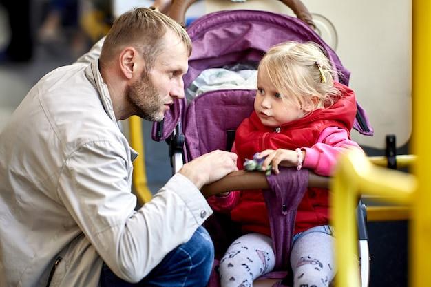 父親と一緒に乳母車の少女がバスに乗っています