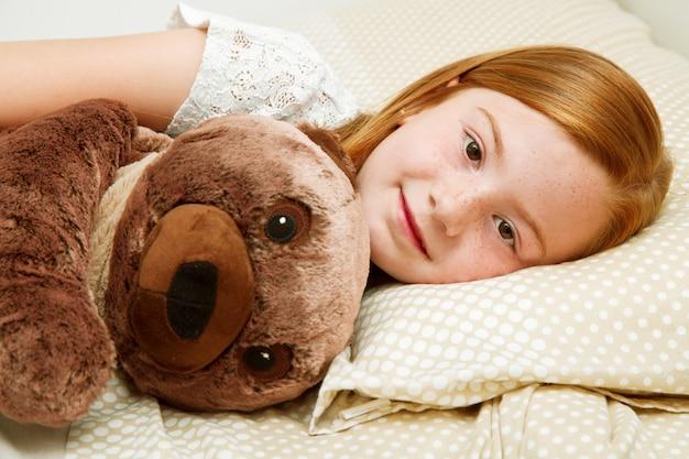 테 디 베어를 안고 침대에서 어린 소녀