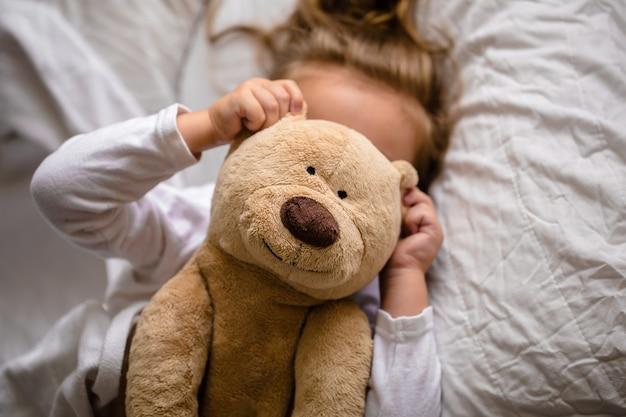 柔らかいおもちゃが付いているベッドの小さな女の子、白いベッドの子供の感情