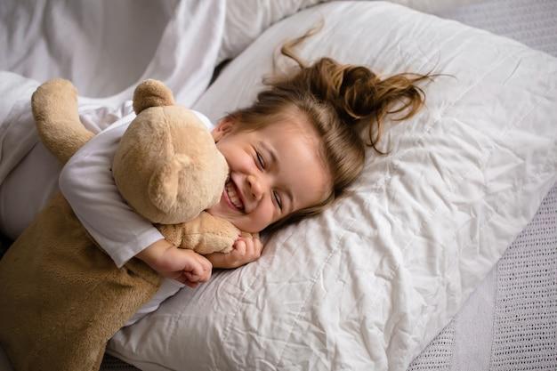 Маленькая девочка в постели с мягкой игрушкой эмоции ребенка