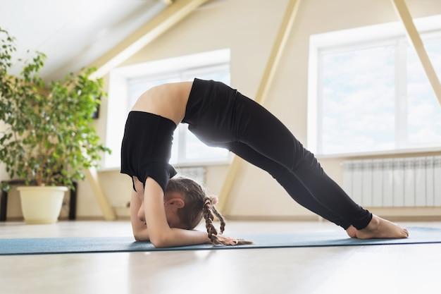 Маленькая девочка в черной спортивной одежде занимается йогой, делая упражнения випарита дандасана, поза локтевого моста на гимнастическом коврике в студии