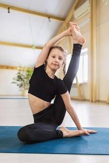 Маленькая девочка в черной спортивной одежде, практикующая йогу, выполняет упражнение сурья янтрасана, сидя в позе компаса на коврике в студии