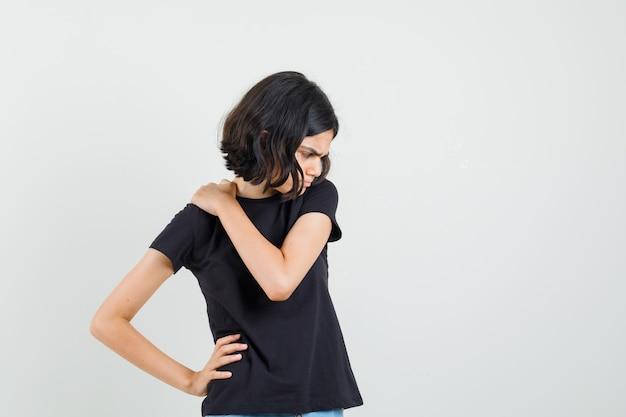 Маленькая девочка в черной футболке испытывает боль в шее и выглядит неудобно, вид спереди.