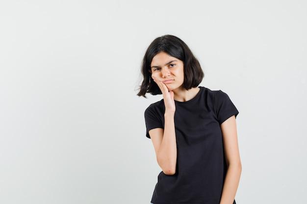 고통스러운 치통이 있고 슬픈, 전면보기를 찾고 검은 색 티셔츠에 어린 소녀.