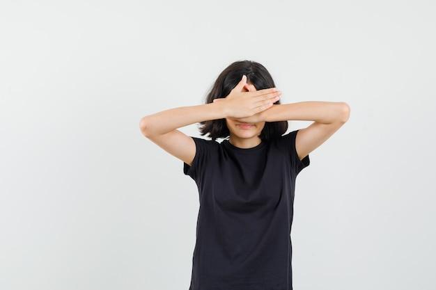 目をつないで恥ずかしそうに見える黒いtシャツを着た少女、正面図。