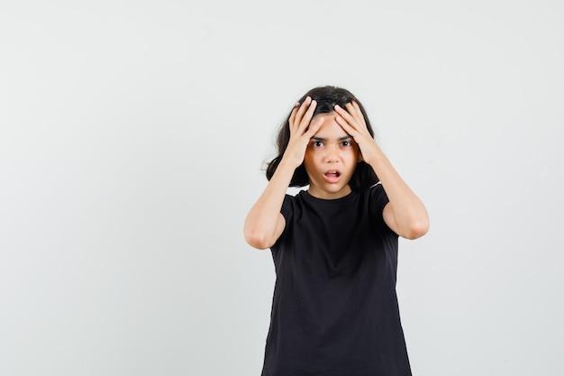 Маленькая девочка в черной футболке, взявшись за руки к голове и глядя печально, вид спереди.
