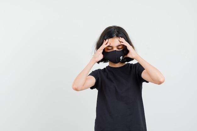 검은 티셔츠에 어린 소녀, 강한 두통이 있고 피곤해 보이는 마스크, 전면보기.