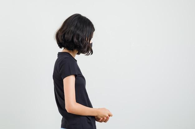 검은 티셔츠에 어린 소녀, 마스크 서 고 진정 찾고.