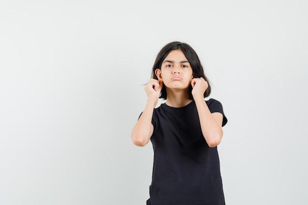 Маленькая девочка в черной футболке опускает мочки ушей и выглядит обиженным, вид спереди.