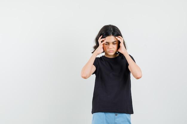 검은 티셔츠에 어린 소녀, 반바지가 강한 두통이 있고 몸이 좋지 않은 모습, 전면보기.