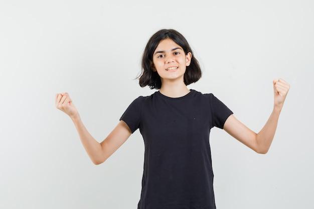 승자 제스처를 표시 하 고 자신감, 전면보기를 찾고 검은 티셔츠에 어린 소녀.