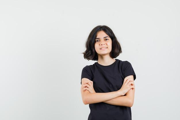 Маленькая девочка в черной футболке, стоящей с крестами на руках и уверенно выглядящей, вид спереди.