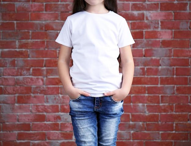 Маленькая девочка в пустой белой футболке, стоя у кирпичной стены