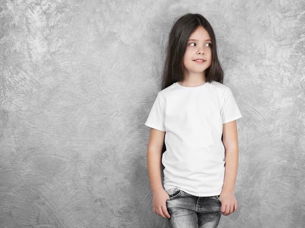 Маленькая девочка в пустой белой футболке, стоящей на серой текстурированной стене