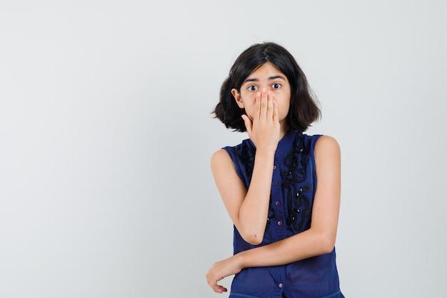 Маленькая девочка в синей блузке, взявшись за рот и удивленно глядя, вид спереди.