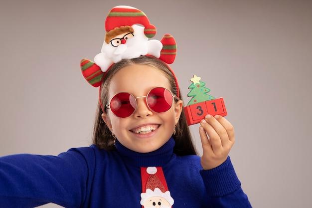 Маленькая девочка в синей водолазке в забавной рождественской оправе на голове держит игрушечные кубики с новогодней датой, счастливая и взволнованная, стоя над белой стеной