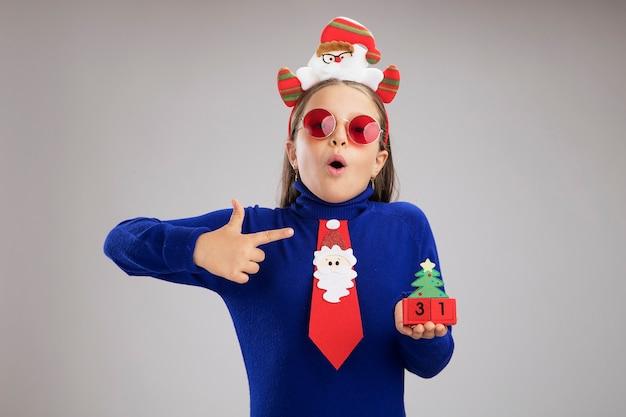 頭に面白いクリスマスの縁を身に着けている青いタートルネックの少女は、白い背景の上に立っているキューブを人差し指で指して驚いて見える幸せな新年の日付でおもちゃのキューブを保持しています