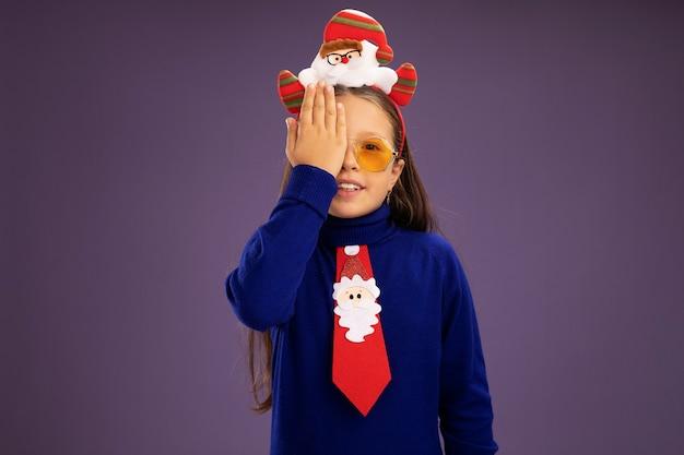 Маленькая девочка в синей водолазке с красным галстуком и забавной рождественской оправой на голове, закрывающей один глаз, с рукой, стоящей над фиолетовой стеной