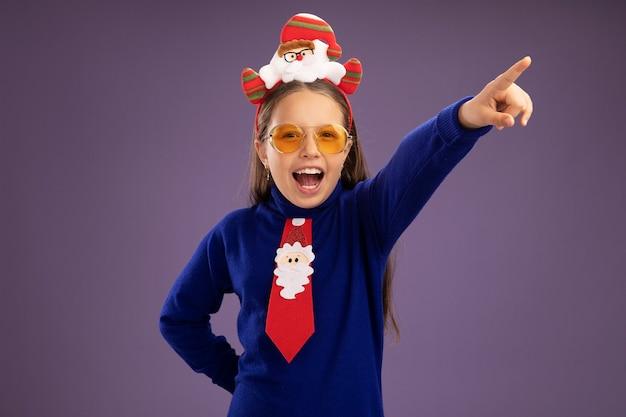 Маленькая девочка в синей водолазке с красным галстуком и забавной рождественской оправой на голове счастлива и взволнована, глядя в камеру, указывая указательным пальцем в сторону, стоя на фиолетовом фоне