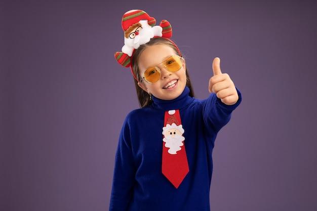 赤いネクタイと面白いクリスマスの縁に赤いネクタイとピンクの壁の上に立って親指を示す幸せで前向きな笑顔の青いタートルネックの少女
